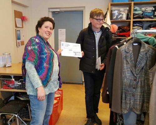 Leerling de Ambelt overhandigt cheque aan Stichting Kledingbank Deventer